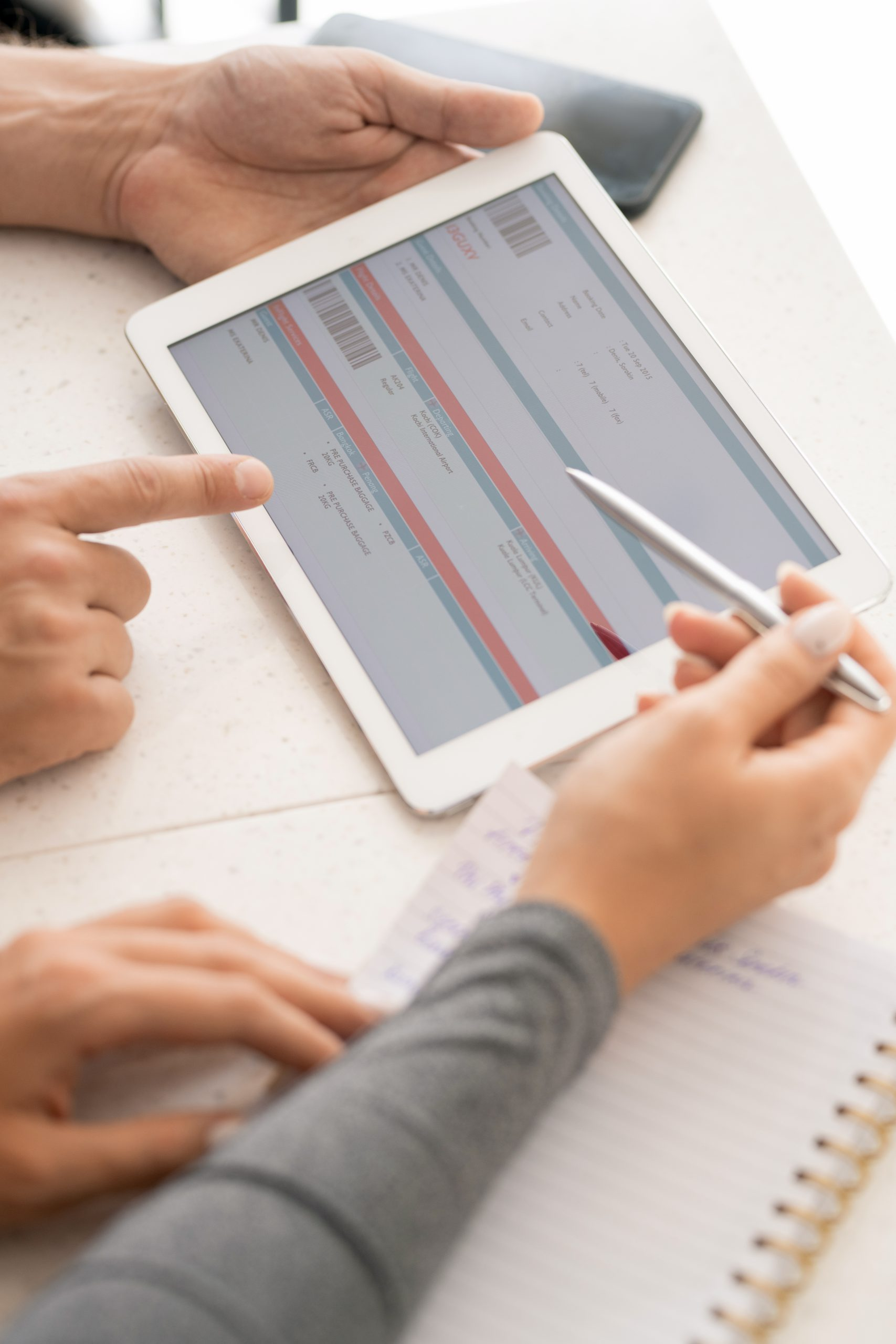 Hands of two young contemporary colleagues discussing online financial information in digital tablet at working meeting